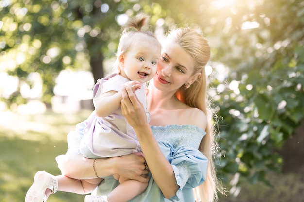 그녀의 아기 소녀와 함께 웃고 있는 젊은 아름다운 금발 어머니
