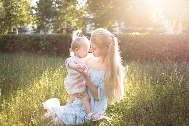 一緒に笑っている彼女の女の赤ちゃんと若い美しいブロンドの母親