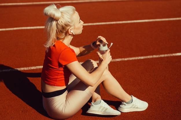Молодая красивая блондинка сидит на беговой дорожке с бутылкой воды в руках
