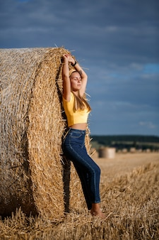 A young beautiful blonde stands on a mown wheat field near a huge sheaf of hay, enjoying nature. nature in the village