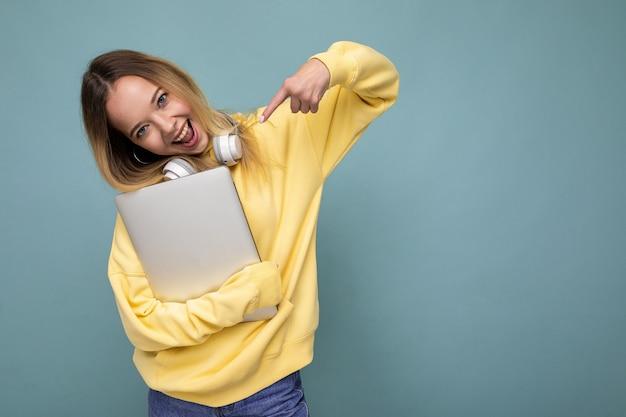 Молодая красивая белокурая студентка в модной желтой толстовке с капюшоном и наушниками, держащая ноутбук