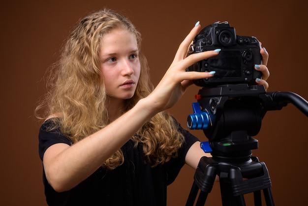 Молодая красивая блондинка девочка-подросток на коричневом