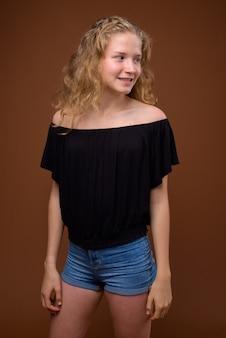 茶色に笑って若い美しい金髪の10代の少女