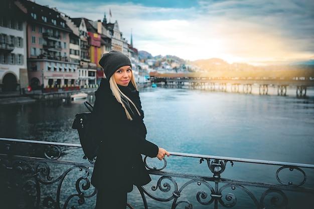 유럽의 추운 가을에 따뜻한 모자와 코트를 입은 젊고 아름다운 금발 관광 소녀