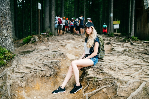 Young beautiful blonde traveler girl portrait.  tourist woman in camping trip.  walking up the hiils.