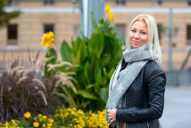 Молодая красивая блондинка женщина против городского кирпичного здания с цветущими кустарниками и многолетниками
