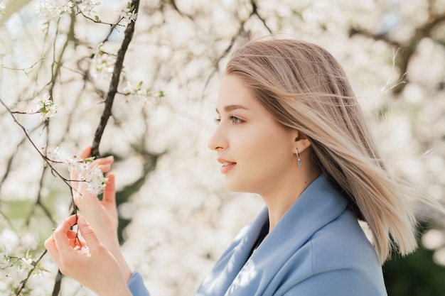 Young beautiful blonde woman in blooming apple garden.