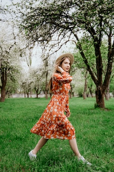 Young beautiful blonde woman in blooming garden. spring trees in bloom. orange dress and straw hat.