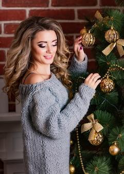 若い美しいブロンドの女性はクリスマスツリーを飾る。正月飾り。ごちそうの準備。グレーのニットのセーターの女の子。