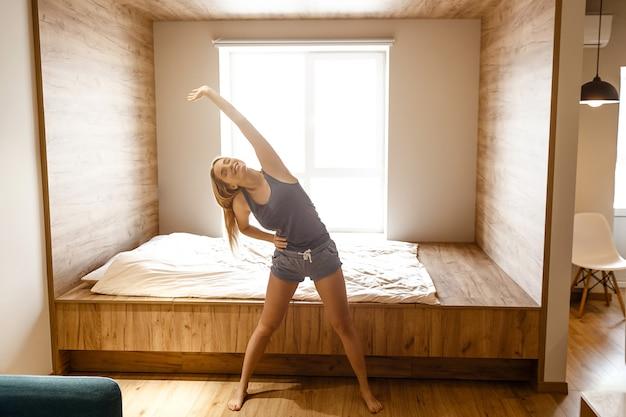朝の家の練習をしている若い美しいブロンドの女性。彼女は部屋に立って横になります。体を伸ばします。一人で。明け。