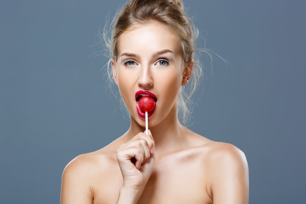 Young beautiful blonde woman eating lollipop