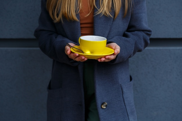 Young beautiful blonde woman in a gray coat drinks hot tea from a yellow cup on a cold autumn day. delicious warm drink on the terrace in the cafe