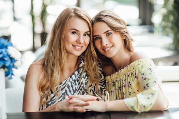 Una giovane bella donna bionda e la sua bella mamma riposano su un caffè con terrazza estiva