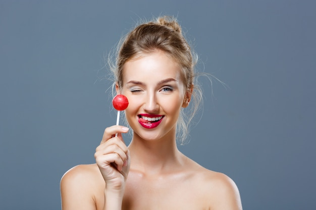 Young beautiful blonde woman holding lollipop