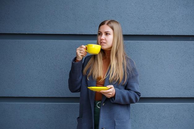 Молодая красивая блондинка в сером пальто пьет горячий чай из желтой чашки в холодный осенний день. вкусный теплый напиток на террасе в кафе