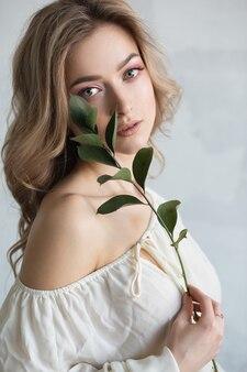 그녀의 손에 꽃과 흰 드레스에 젊은 아름 다운 금발 여자. 패션 초상화 클로즈업