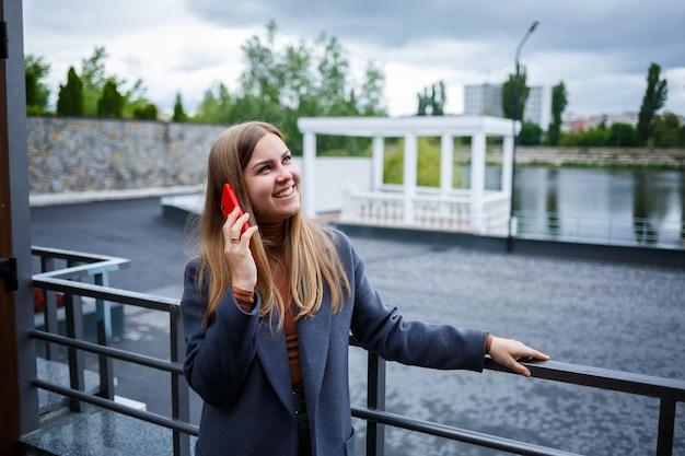 寒い秋の日に電話で話している灰色のコートを着た若い美しいブロンドの女性。川を見下ろすテラスで電話を持つ少女