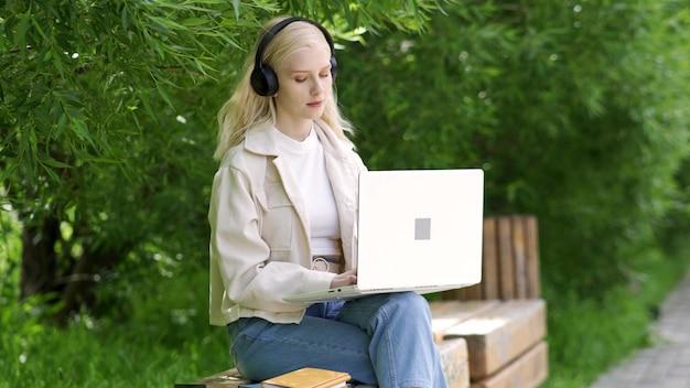 ヘッドフォンで若い美しいブロンドの女性は、ラップトップで公園のベンチに座っています。暖かい夏の日に屋外で作業します。 4k uhd
