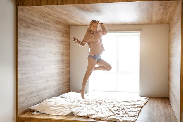 젊은 아름 다운 금발 여자는 오늘 아침 침대에 뛰어. 아주 행복한 모델은 헤드폰을 통해 음악을 듣습니다. 그녀는 전화를 손에 쥐고있다. 일광.