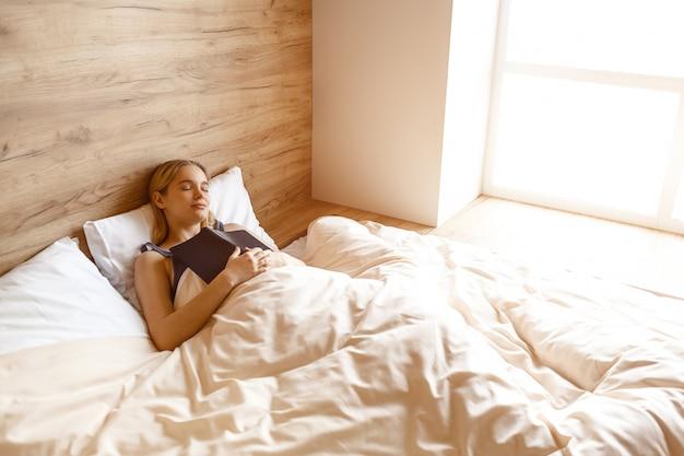 아침에 침대에 누워있는 젊은 아름 다운 금발 여자. 그녀는 자요 가슴에 모델 홀드 책. 좋은 아침. 일광.