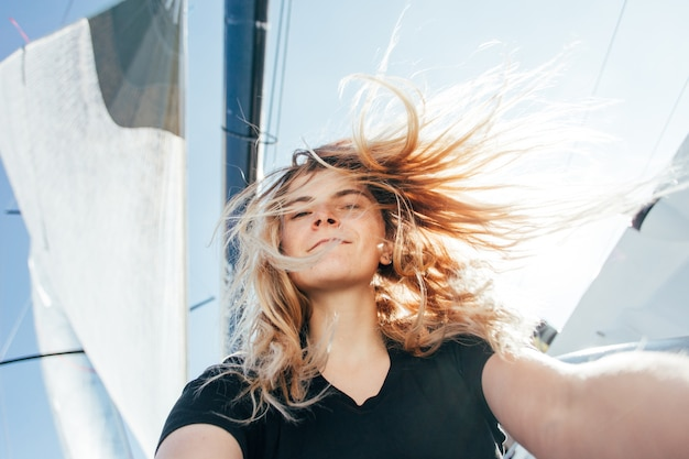 Young beautiful blonde woman makes selfie on sailboat or yacht