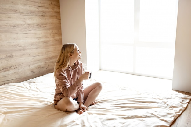 Young beautiful blonde woman sit on bed this morning. her legs crossed. she look at window. model hold cup of hot drink.