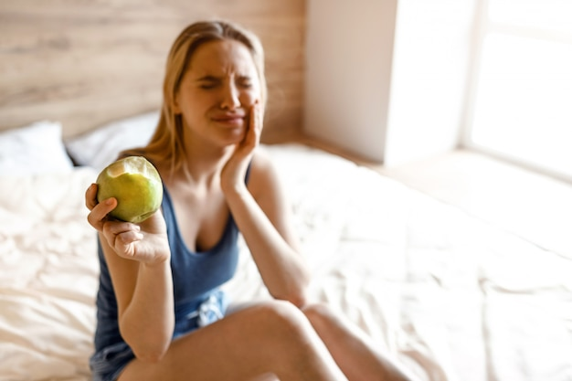 Young beautiful blonde woman sitting in bed in morning. model suffer from tooth ache. she hold hand on cheek. bitten apple in another hand. she show it to camera.