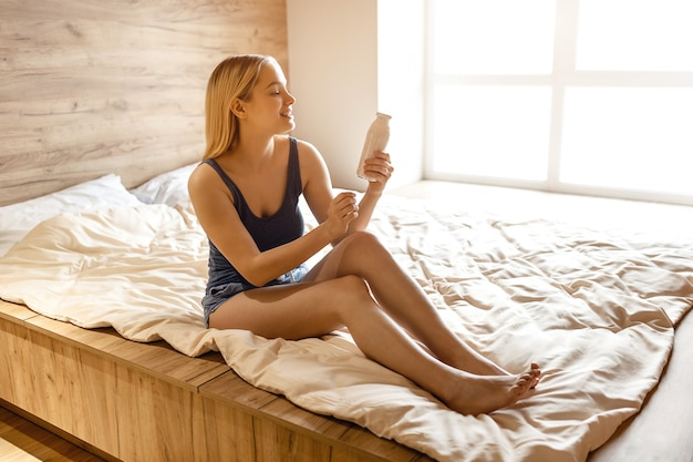 Young beautiful blonde woman sitting in bed in morning. she hold glass bottle in hand and look at it. she smile. daylight.