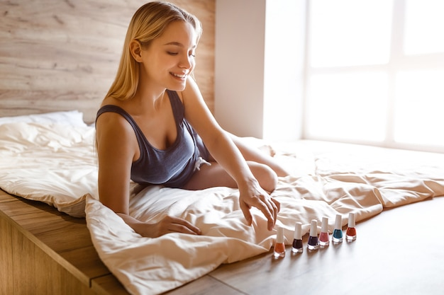 Young beautiful blonde woman sitting in bed in morning. she look at colorful nail polish. she look at it and smile. she pick up color.