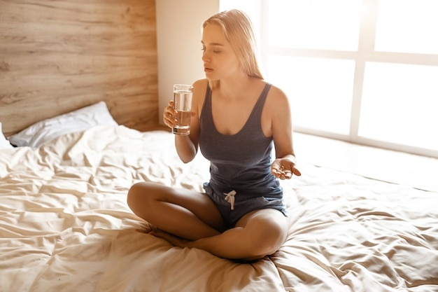Young beautiful blonde woman sitting in bed in morning. she sit in lotus pose and drink water from glass. young woman has pill in hand. serious and concentrated.