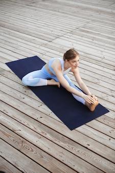 Молодая красивая белокурая женщина усмехаясь, практикуя йогу снаружи