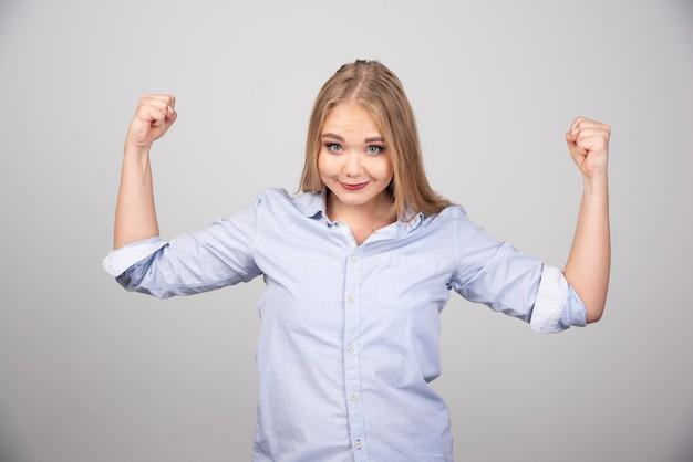 立って腕の筋肉を見せている若い美しいブロンドの女性。