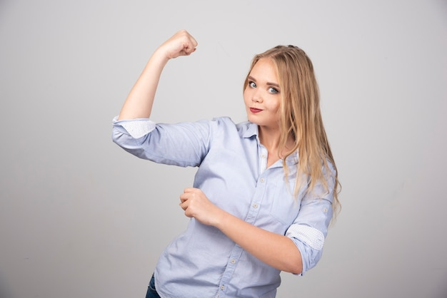 Young beautiful blonde woman standing and showing arm muscle.