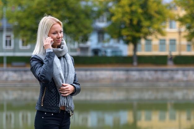 강을 따라 공원에서 휴대 전화로 이야기하는 젊은 아름다운 금발의 여자