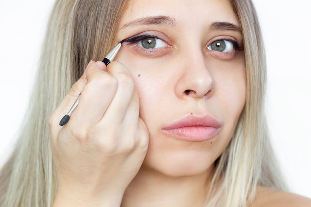 A young beautiful blonde woman using a contour brush while drawing arrows on the eyelids isolated. a girl makes a makeup herself at home
