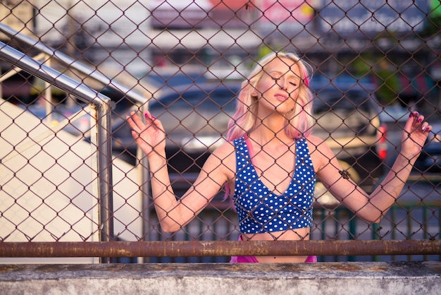 Young beautiful blonde woman with eyes closed while holding chain link fence outdoors
