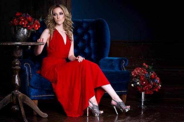 青いソファの上の豪華なインテリアでポーズをとって赤いドレスのプロのメイクと髪型を持つ若い美しいブロンドの女性