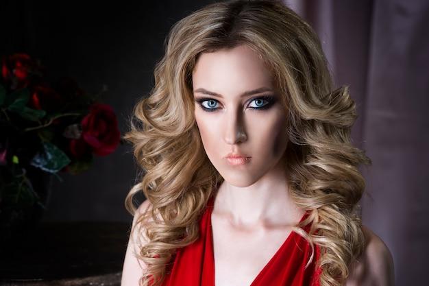 赤いドレスのプロのメイクと髪型を持つ若い美しいブロンドの女性