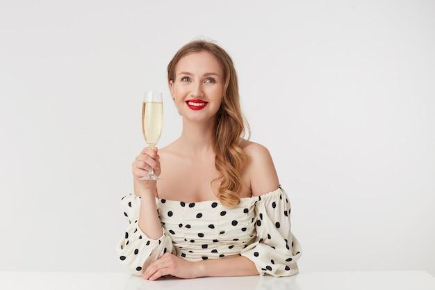 Giovane bella ragazza dagli occhi azzurri con lunghi capelli biondi, con labbra rosse, posa al tavolo con un bicchiere di champagne, guarda scherzosamente lontano, sognando, sorridente, isolato su sfondo bianco.