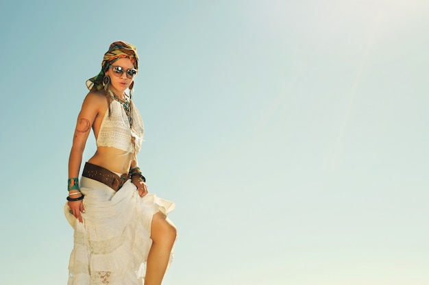 Young beautiful boho style woman standing outdoor against sky, vintage bleached colors