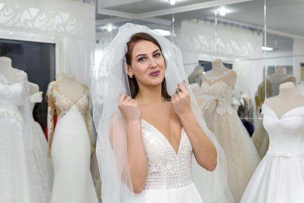 Молодая красивая невеста, выбирая платье и вуаль в салоне