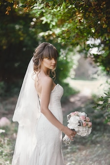 Young beautiful bride in an elegant dress is standing on the field near the forest and holding bouquet of pink flowers and greens with ribbon at nature. outdoors. after the wedding ceremony.