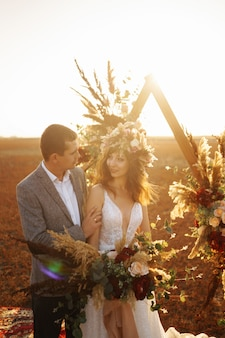 Young and beautiful bride and groom enjoy each other. wedding day in boho style.