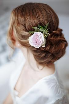 新鮮な花と若い美しい花嫁の髪型。