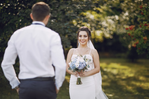 A young and beautiful bride and her husband standing in a summer park with bouquet