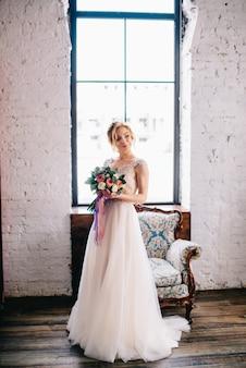 꽃다발을 들고 다락방에서 창 앞에 서있는 젊은 아름다운 신부