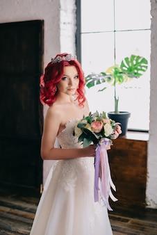 꽃다발을 들고 다락방의 창 근처에 서있는 젊은 아름다운 신부