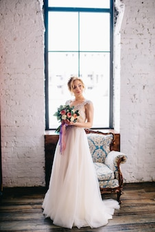 Young beautiful bride holding a bouquet and standing in front of a window in the loft