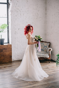 Young beautiful bride holding a bouquet and standing near the window in the loft