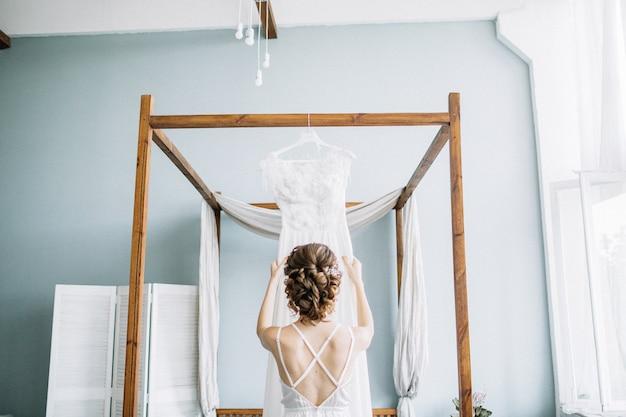 Молодая красивая невеста держит свадебное платье